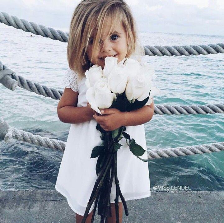 Bébé avec un beau bouquet de roses blanches pour les cérémonies