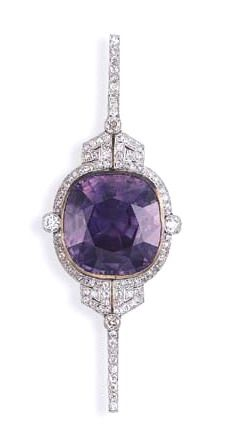A RARE COLOR CHANGE SAPPHIRE AND DIAMOND BROOCH  Set with a cushion-cut color change sapphire, weighing approximately 76.11 carats, within an openwork pierced pavé-set plaque of geometric design, mounted in platinum-topped gold.