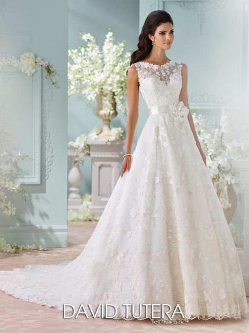 David Tutera for Mon Cheri - 116218 – Kyra - Wedding dress with lace back, seeveless Schiffli lace appliqués, organza, tulle and sequin tulle over satin A-line gown, illusion and lace bateau neckline over sweetheart bodice, satin natural waistband with three-dimensional flower, illusion and lace back bodice with covered button closures, scalloped hem with chapel length train.  Sizes: 0 – 20, 18W – 26W  Colors: Ivory/Champagne, Ivory, White