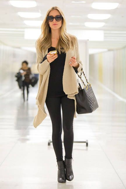Neutral, chunky knit over black leggings for a sophisticated travel look
