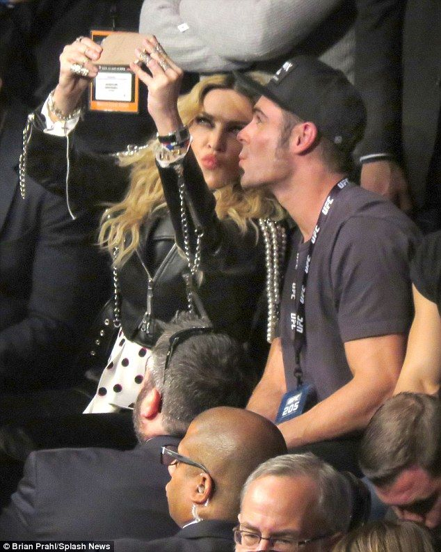 Friendly pair: Madonna was seen getting a kiss from Zac Efron, as the they watched Connor McGregor at Madison Square Garden in New York City on Saturday