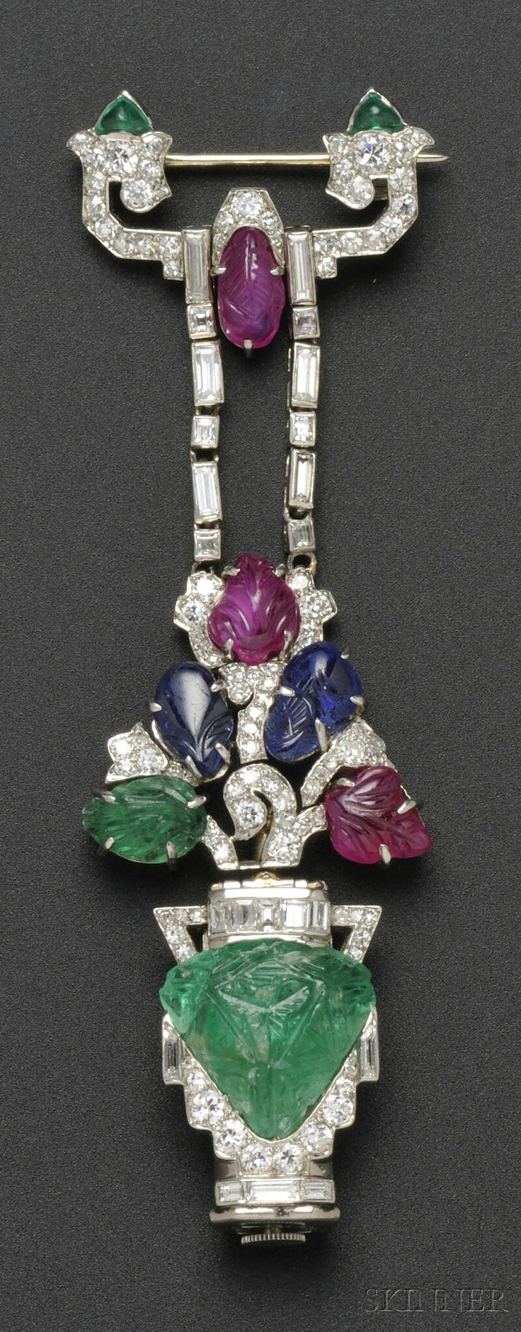 "Art Deco ""Tutti Frutti"" Pendant Watch, Mauboussin, France, designed as a carved emerald flowerpot with carved ruby, sapphire, and emerald blossoms, and transitional-, old single-, baguette-, and fancy-cut diamonds, enclosing 18-jewel manual-wind movement no. 3250, case no. 275, lg. 3 1/8 in., maker's mark and guarantee stamps, signed movement and watch case. @Deidra Brocké Wallace"