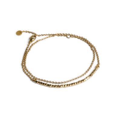 Pärlarmband med kedja i förgyllt silver. Armbandet består av en stav med förgyllda silverpärlor samt en ankarkedja. När armbandet tas på viras det två varv runt handleden och knäpps med ett karbinlås. Armbandets design ger ett minimalistiskt och elegant intryck.