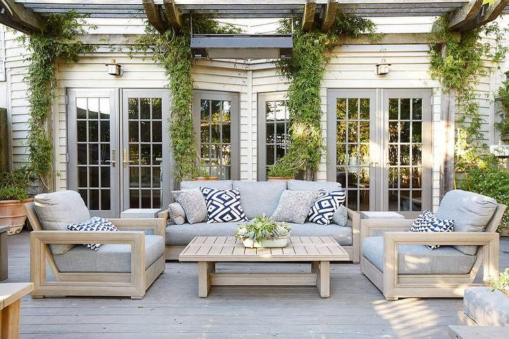 A black pergola attached to the house provides shade for a Restoration Hardware Costa Classic Sofa and Costa Classic Chairs lined with blue geometric outdoor pillows facing a Costa Coffee Table.