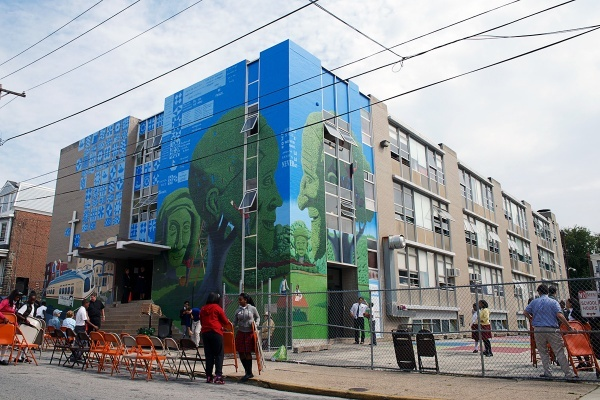 The 80-by-40 foot mural by Mark Elder (and a slew of helpers) wraps around the northwest corner of the DePaul Catholic School in Germantown. (Bas Slabbers/for NewsWorks)