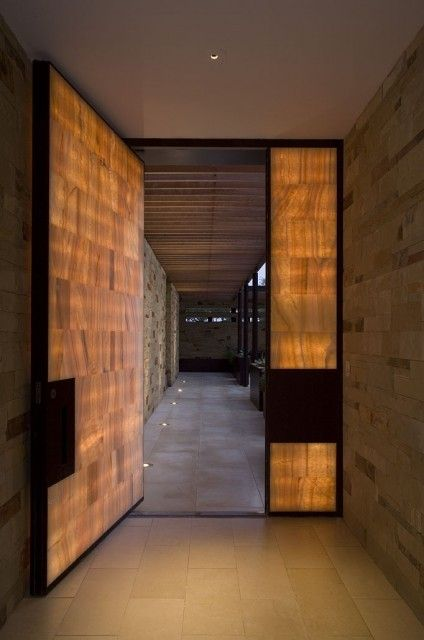 This front door contains backlight honey onyx tiles in a steel frame, setting it permanently aglow.