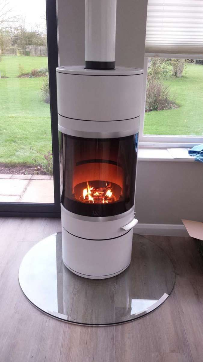 scan 83 in white with chrome trim, on a clear glass hearth, installed by Central Stoves