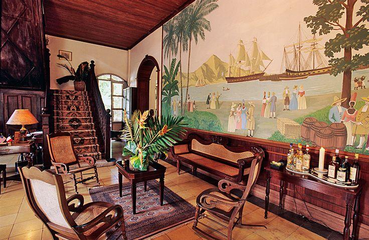 Типичный колониальный интерьер —мебель из красного дерева и ротанга, ковры и циновки ручной работы, статуэтки