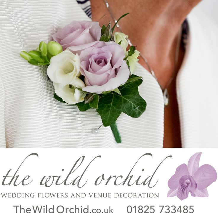 A lady's corsage ideal for the mother of the bride or groom. Lilac roses, white lisianthus, ivory spray roses and white freesia backed by ivy leaves and secured with a pin and magnets.