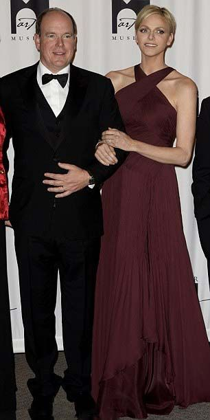 Monaco's Prince Albert II and his wife Princess Charlene looked elegant in a floor-length burgundy dress, her blond locks swept off her face into a chic chignon at the opening of an exhibition on 26.10.13.