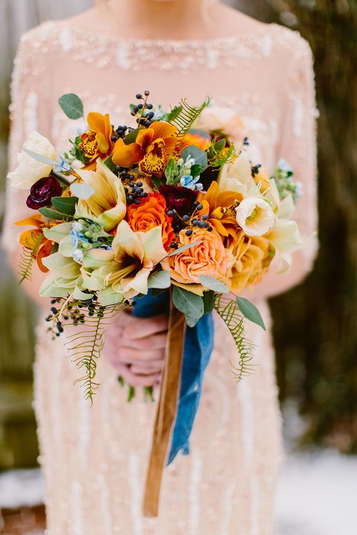 Bridal bouquet featuring mocha amaryllis, blue tweedia, finess roses, combo roses, free spirit roses, white poppies, privet berry, sea star fern, silver dollar eucalyptus, burgundy ranunculus and orange cymbidiums by Sebesta Design. Photo by Redfield Photo.