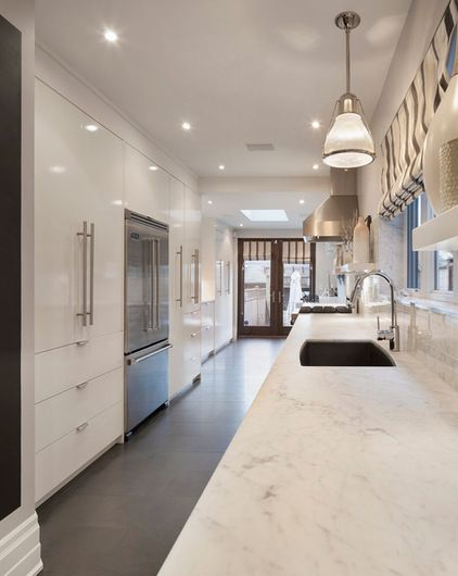 The marble countertops were honed to a matte finish, replacing the previous glossy look. New pendants and a Roman shade also help the kitchen feel more contemporary.