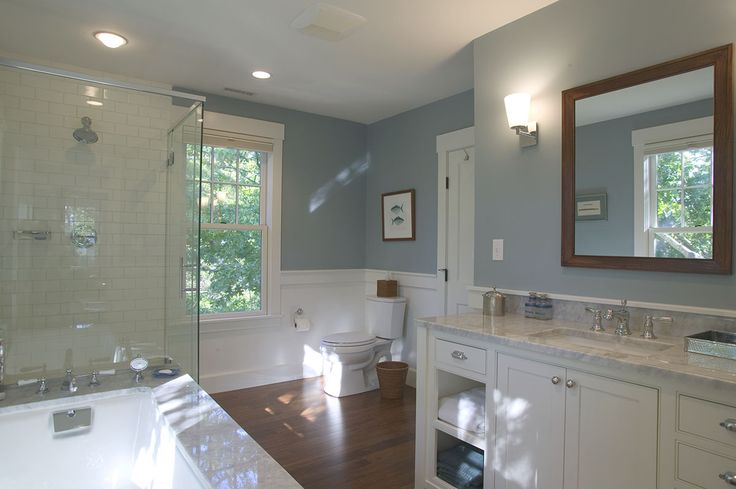 Custom built Cape Cod luxury bathroom with hardwood flooring and white tile glass enclosed shower. By Cape Associates, Inc.