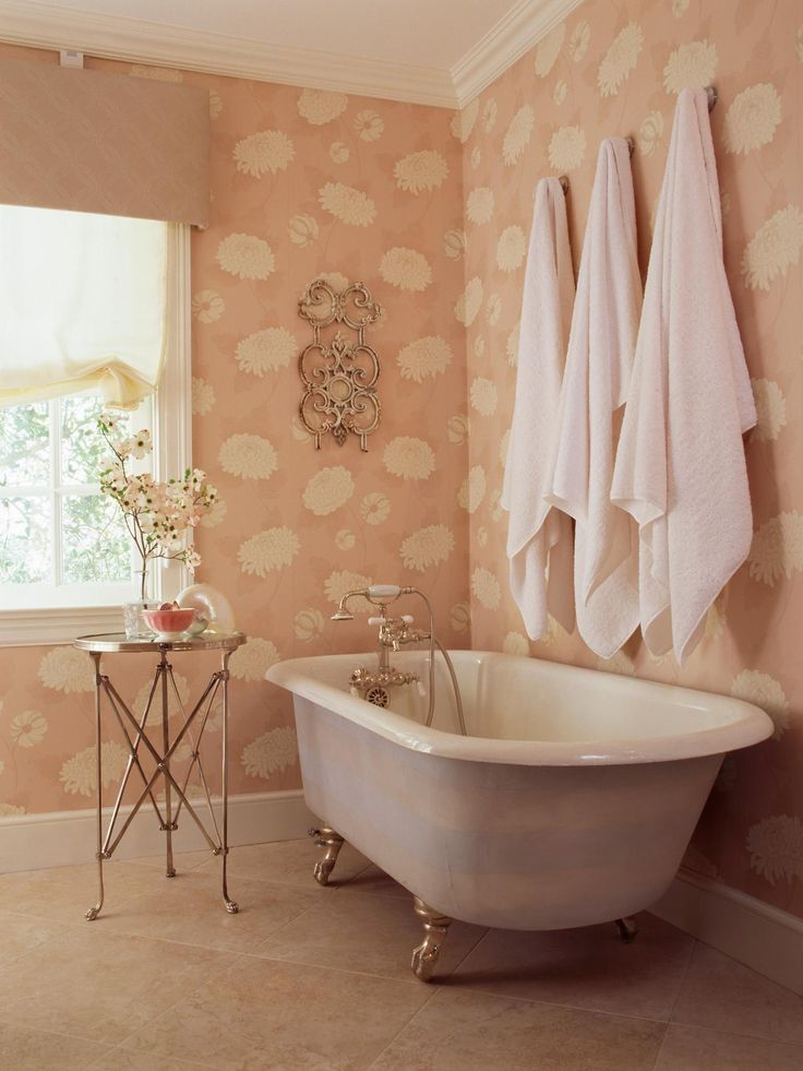The claw foot tub in this cottage-style bathroom is the perfect place to relax and unwind. A soft blush wallpaper with cream colored flowers adds to the femininity of the space.
