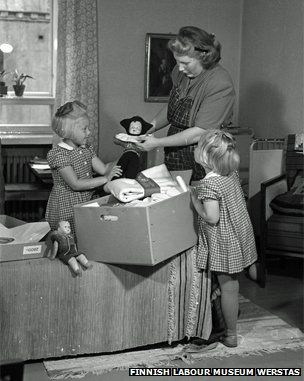Mother and daughters look at a Finnish maternity pack from 1947