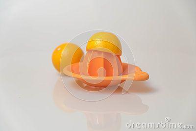 Orange lemon juicer with lemons.