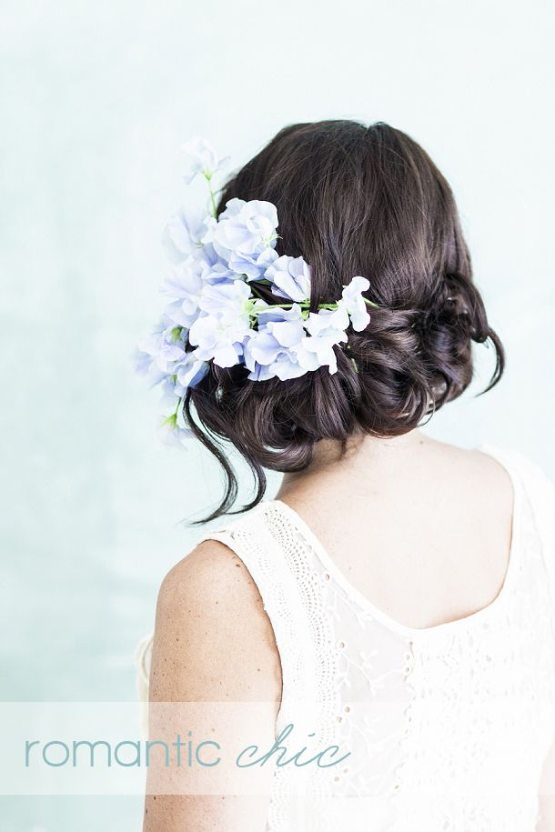 This soft playful, updo is beautifully adorned with a spray of sweet-scented lilac sweetpeas, giving an asymmetrical feel. Perfect for a romantic bride that loves a fabulous vintage dress and a stylish wedding venue