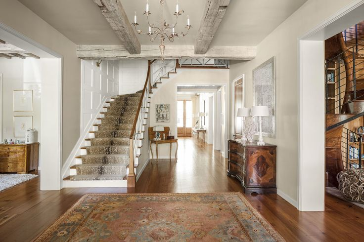 Grand staircase entrance with patterned stair runner, farmhouse beams, antique tole chandelier and warm wood flooring and large scale rug. Collins Interiors
