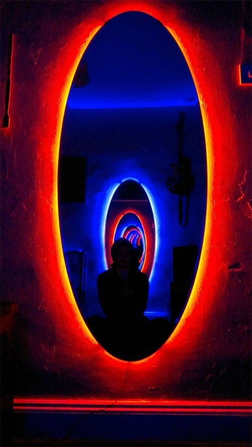 LED lighting strips around oval mirrors.
