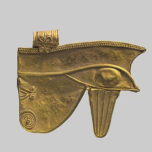 """Wedjet eye, Ptolemaic Period (ca. 304–30 b.c.)  Egyptian  Gold  The wedjat-eye amulet represents a human eye with its brow, but the two lines below the eye are often identified as the facial markings of a falcon. The wedjat-eye was supposedly the eye that Seth tore from Horus during a battle over who would lead the gods. Thoth healed the injured eye, returning it to Horus as the """"sound one."""" Wedjat-eye amulets were used fro..."""