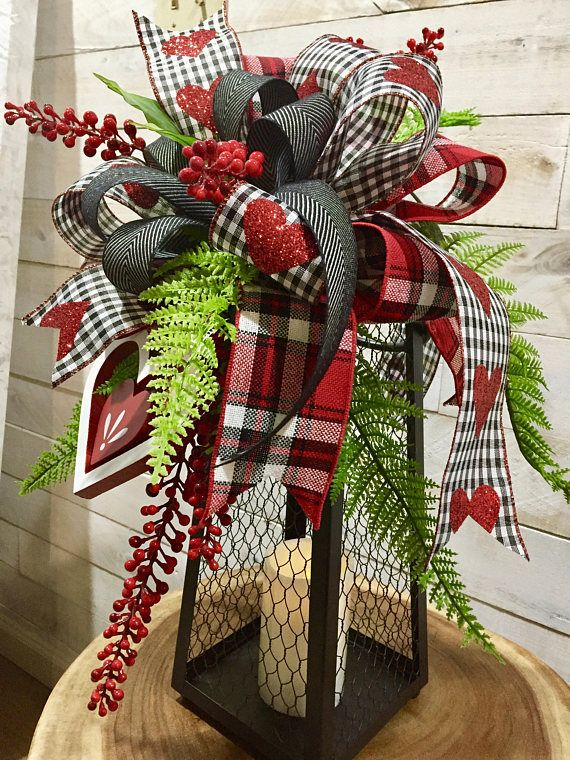 This large sized, beautifully designed Valentines Day Lantern Swag features an assortment of designer ribbons in red, white and black plaid, shimmering red heart black and white gingham , and black and white herringbone, accented with stems of vibrant red berries. Vibrant green forest
