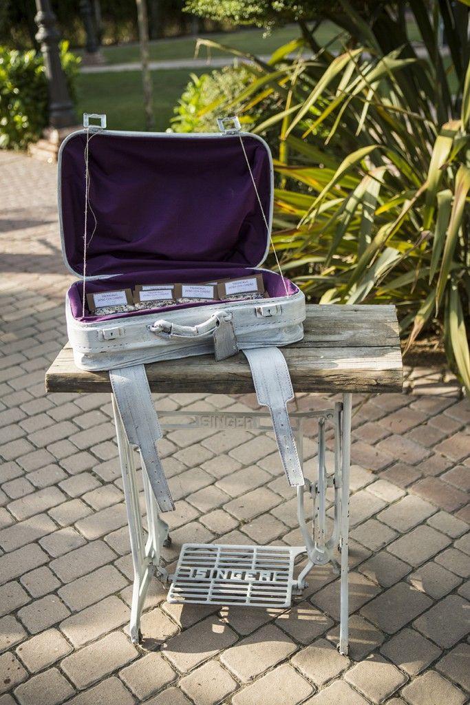 Mesa reciclada de máquina de coser sobre la que colocamos una maleta antigua para colocar paquetitos de arroz para la boda. #paquetitosarroz #decoraciónboda