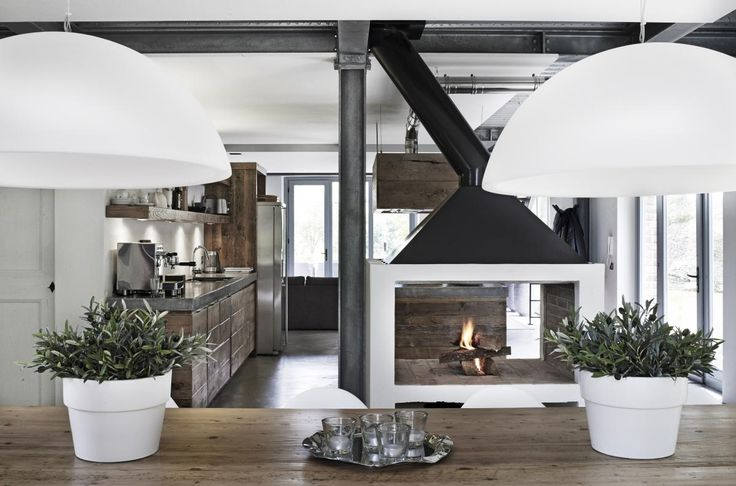 Kjøkkenet har en stor, åpen peis som virker som naturlig romdeler mot spisestuen. Den svarte skorsteinen er helt i tråd med huset industrielle stil, med synlige stålbjelker og hvitevarer i rustfritt stål. Kjøkkenet har en lokal snekker bygget av gjenbrukstre i en varm tone.   Foto: Krisian Septimus Krogh