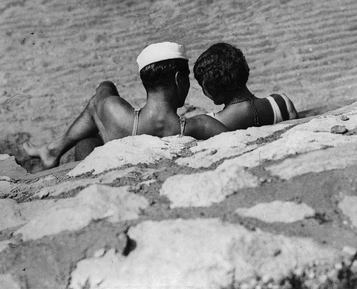 Una coppia prende il sole in spiaggia in una località non specificata, negli anni Trenta. (General Photographic Agency/Getty Images)