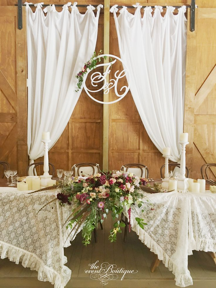 Bridal table styled with frilled vintage lace tablecloth, pillar candles and florals. We designed the entwined initials of the bride and groom which were laser cut, painted and installed above the table, finished with a floral garland.