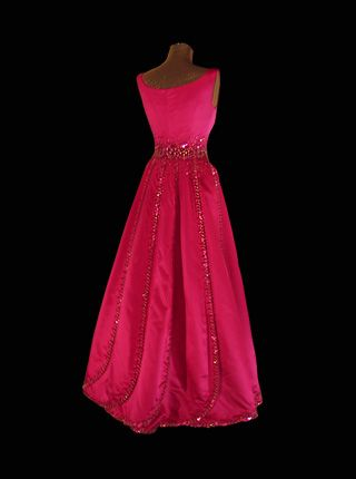 1988 - This cerise-coloured duchesse gown designed by Jørgen   Bender, Copenhagen, is   adorned with sequins and rhinestones. The panels of the skirt are trimmed with rhinestones and overlap each other like petals. Worn by Queen Silvia of Sweden to Nobel Banquet.