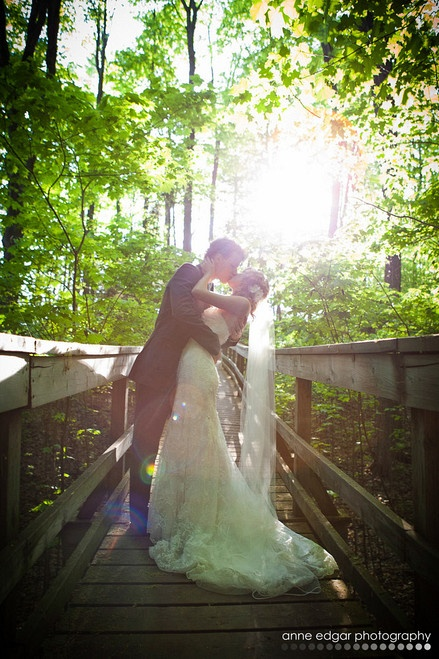 wedding photo, couple kissing on bridge in forest
