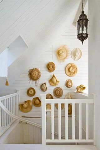 Summery white decor with straw hats massed on a shiplap white staircase wall. #summerstyle #stawhats #rusticdecor #staircase