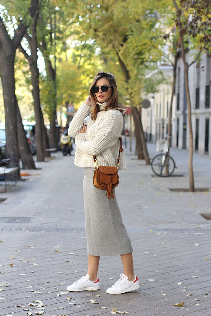 Knitwear can be worn with sneakers for a more casual, unconventional style. Silvia Zamora wears a grey knit midi skirt with white adidas trainers and a cropped cream knit sweater.