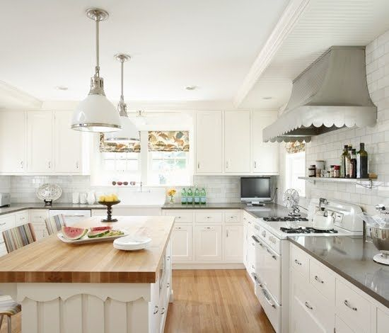 A Custom Scalloped Stainless Steel Hood Wall Mounted Onto White Subway Tiles  Over A Vintage Looking