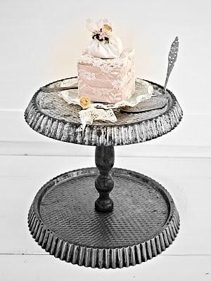 Etagere van bakblikken met een gebakje van kant