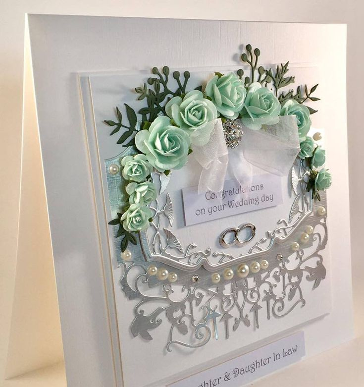 A stunning gay wedding card for the ladies in the classically elegant colour combo of white and silver with accents of duck egg blue roses. An ornate centre topper die cut in matt silver linen card with the corsage of roses forms the focal point with a white organza bow and faux diamante cluster to
