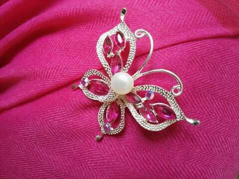 Silver-colored butterfly brooch with pink stones and freshwater pearl.