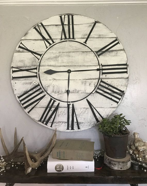 Handcrafted, rustic oversized farmhouse wall clock with Roman Numerals. This clock is assembled with wood. The wood on it has been sanded lightly, but left with is rustic characteristics. This clock will add the perfect accent to your living room, kitchen or bedroom! The first clock shown is 30 in diameter and has been left natural The last clock shown is 36 and has been left natural as well. ***Depending on the size of the clock chosen, there may be an outside white circle,matching the…