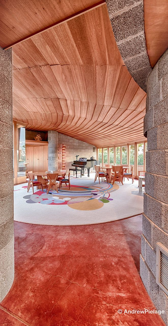 A living room designed by Frank Lloyd Wright. A piano and two midcentury dining sets sit on a graphic rug.