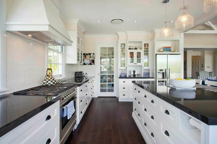 The kitchen is in white with glossy black granite countertops and a large, high-end range. A glass-faced door leads out of the kitchen and into another room in the home.