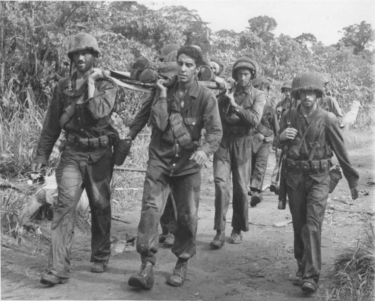 """""""Bringing Home the Wounded – American soldiers on the Soputa front near Buna, New Guinea, bear their wounded to headquarters as they return from 11 days fighting the Japs. Note the automatic gun by the soldiers side on the stretcher."""" Associated Press photo 12-24-42."""""""