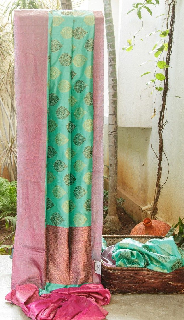 TURQUOISE BLUE SILK BENARAS IS ENHANCED WITH PINK AND GOLD TISSUE BORDER AND PALLU. THE TRADITIONAL MOTIFS IN GOLD AND ANTIQUE GOLD ACCENTUATE THE SAREE