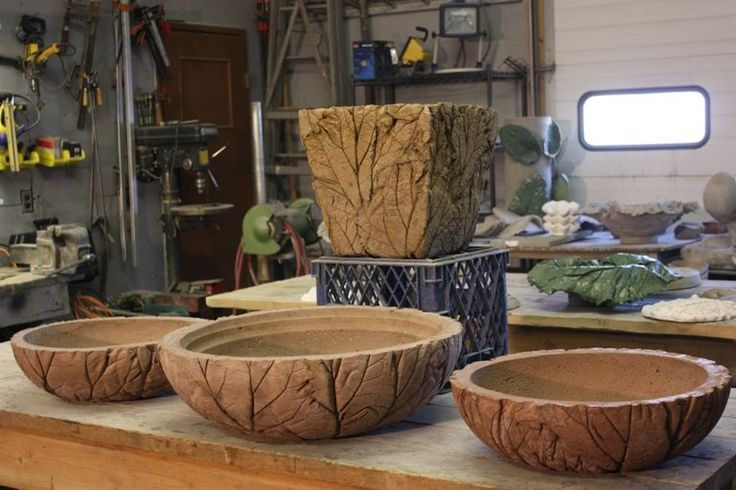 Concrete leaf bowls.  Made by pressing leaves on outside and placing another bowl or box on top to create pressure to embed the design into the wet concrete.