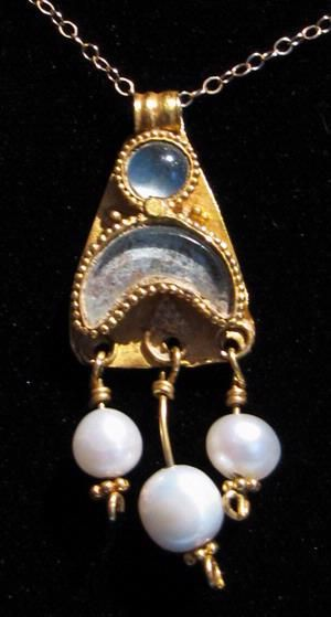 Greek Gold Pendant with Pearls An ancient Greek gold pendant with a solar and lunar motif inlaid with aquamarine and three dangling antique natural pearls, ca 4th century B.C.