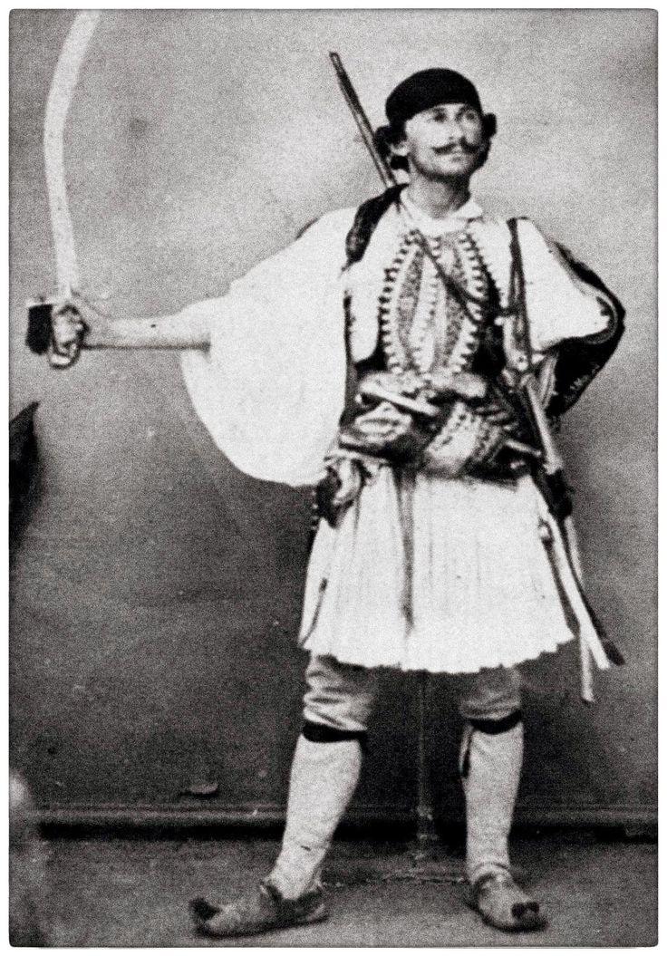 Π. Μωραΐτης. Ο ληστής Κυριάκος υπήρξε ο φόβος των κατοίκων της Αττικής, γι' αυτό και είχε επικηρυχθεί με μεγάλο ποσό. Κατά τα «Ιουνιακά» του 1863 ήρθε στην Αθήνα με τη συμμορία του για να ενισχύσει τους «Πεδινούς». Με την ευκαιρία λήστεψε όλους τους ξένους ταξιδιώτες που έμεναν στα ξενοδοχεία της πλατείας Κοτζιά. Τότε πρέπει να επισκέφθηκε το φωτογραφείο του Μωραΐτη για μια στημένη «ηρωική» πόζα.