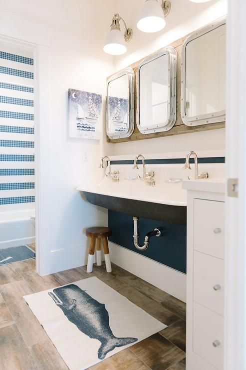 Shared kids' cottage bathroom features three Restoration Hardware Submarine Inset Medicine Cabinets over a black trough sink, Kohler Brockway 5' Sink, fitted with three gooseneck faucets alongside a Serena & Lily Dip Dyed Stool atop a blue whale bath mat rug, Thomas Paul Moby Bath Mat.