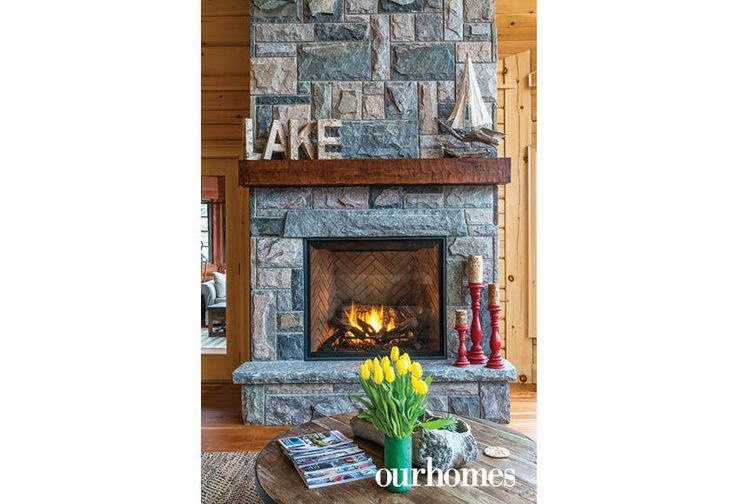 """Granite veneer sheaths the propane fireplace.    See more of this home in """"Fifth Generation Legacy on Muskoka's Moon River"""" from OUR HOMES Muskoka Early Summer 2017: http://www.ourhomes.ca/articles/build/article/fifth-generation-legacy-on-muskokas-moon-river"""