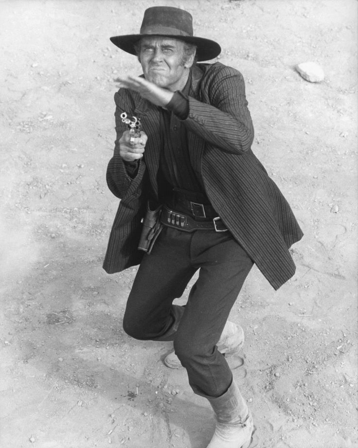 ONE UPON A TIME IN THE WEST - Henry Fonda fans off some shots - Directed by Sergio Leone - Paramount - Publicity Still.