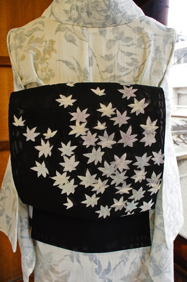 黒の地に星のようにも見えるキラキラシルバーの紅葉の枝葉が織り出された涼やかな紗の夏帯です。