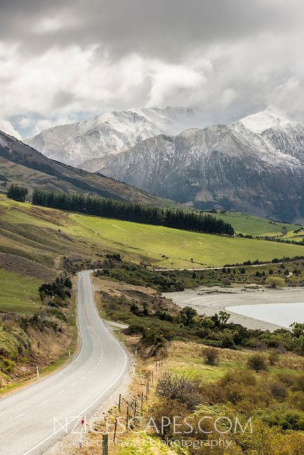 Scenic road along Lake Wanaka surrounded by snow covered mountains, Central Otago, New Zealand